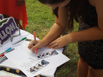 a party guest writes on a scrapbook page