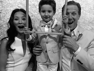 a family with a young son pose for a photo in the picture booth