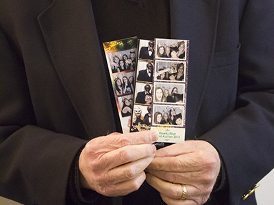 a man in a suit holding three photo strips