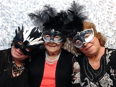 three older ladies pose with masks in the photobooth