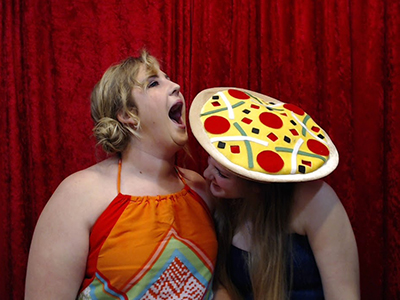two girls playing with silly props in the picture booth