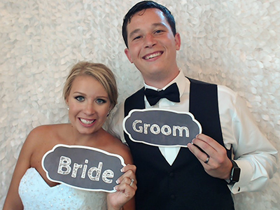 a bride and groom pose for a sweet picture in the photo booth