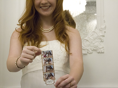 a bride poses with her photo strip