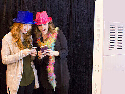 two friends share photos on their smart phones outside the photo booth